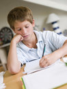 Young Boy Doing Homework In His Room Royalty Free Stock Image
