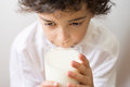 Young boy drinking a glass of milk diet source of calcium boy getting his daily portion of milk and calcium child with curly hair Royalty Free Stock Photos