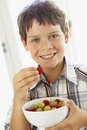 Young Boy Eating Bowl Of Fresh Fruit Stock Photo
