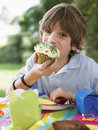 Young boy eating cupcake at birthday party portrait of little the outdoor Stock Image