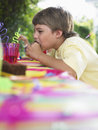 Young boy eating cupcake at birthday party side view of little the outdoor Royalty Free Stock Photos