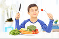 Young boy eating healthy meal seated at table a Royalty Free Stock Images