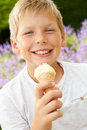 Young boy eating ice cream outdoors smiling at camera Stock Photo