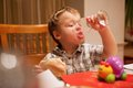 Young boy enjoying lunch draining the last drops of liquid from a glass as he holds a pie in his other hand Royalty Free Stock Photos