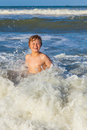 Young boy enjoys the waves of the blue sea happy Stock Image