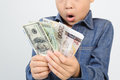 Young boy excite with bank note out focus face excitewith american and korean in his hand Stock Photo