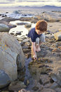 Young boy exploring on the beach a toddler with red hair and picking up pebbles Royalty Free Stock Image