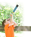 Young boy exploring nature magnifying telescope looking up there green grass white edges copyspace Royalty Free Stock Photos