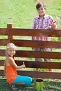Young boy and girl painting a wooden fence Royalty Free Stock Photo