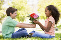 Young boy giving young girl flowers and smiling Royalty Free Stock Photo