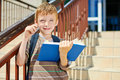 Young boy has an idea thoughtful with book on school stairs Stock Images
