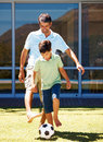 Young boy and his dad playing football Royalty Free Stock Photos