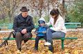 Young boy with his mother and grandfather handicapped elderly playing tablet computer as they sit on bench park on cold autumn day Royalty Free Stock Photography