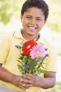 Young boy holding flowers Royalty Free Stock Photo