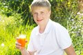 Young boy is holding glass with carrot juice Royalty Free Stock Photo