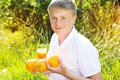 Young boy is holding glass with orange juice and Royalty Free Stock Photo