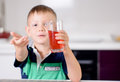 Young Boy Holding Glass of Red Juice Toward Camera Royalty Free Stock Photo