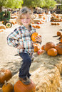 Young boy holding his pumpkin at a pumpkin patch adorable little sitting and in rustic ranch setting the Stock Photography