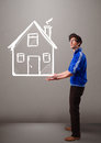 Young boy holding a huge drawn house attractive Royalty Free Stock Image