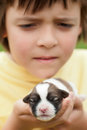 Young boy holding newborn puppy dog with great care closeup shallow depth Stock Photo