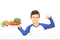 Young boy holding plate full of vegetables and showing muscle isolated on white background Stock Photos