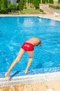 Young boy jumping into swimming pool a is ready to jump Royalty Free Stock Photography