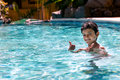 Young boy kid child eight years old having fun in swimming pool leisure activity thumbs up Royalty Free Stock Photo
