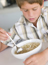 Young boy in kitchen eating soup Royalty Free Stock Photo