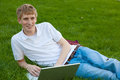 Young boy with laptop computer outside sitting on grass a college age a Stock Image