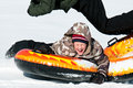 Young boy laughing on a snow tube cute and having fun vacation Royalty Free Stock Photography