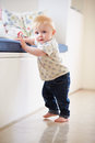 Young Boy Learning To Walk By Holding Onto Furniture Royalty Free Stock Photo