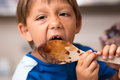 Young boy licking chocolate off a spoon Royalty Free Stock Photography