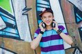 Young boy listening to music close up portrait of happy teens with headphones near painted wall Royalty Free Stock Images