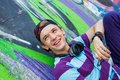 Young boy listening to music close up portrait of happy teens with headphones near painted wall Royalty Free Stock Image