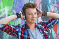 Young boy listening to music close up portrait of happy teens with headphones near painted wall Stock Images