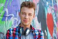 Young boy listening to music close up portrait of happy teens with headphones near painted wall Royalty Free Stock Photos