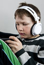 Young boy listening to music earphones wile playing texting cellphone Royalty Free Stock Photos