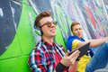 Young boy listening to music portrait of happy teens near painted wall Stock Image