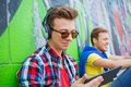 Young boy listening to music portrait of happy teens near painted wall Royalty Free Stock Photography
