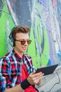 Young boy listening to music portrait of happy teens near painted wall vertical view Stock Image