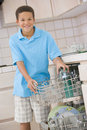 Young Boy Loading Dishwasher Royalty Free Stock Photos
