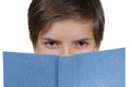 Young boy looking through behind a blue book isolated on white Royalty Free Stock Photography