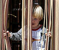 Young boy looking out from behind curtain Royalty Free Stock Photo