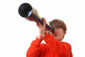 Young boy looks through a telescope on white background Royalty Free Stock Photo
