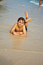 Young boy is lying at the beach and enjoying warmness of water and looking self confident and happy Royalty Free Stock Image