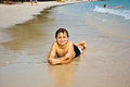 Young boy is lying at the beach and enjoying warmness of water and looking self confident and happy Royalty Free Stock Photography