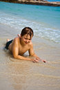 Young boy is lying at the beach and enjoying warmness of water and looking self confident and happy Stock Photos