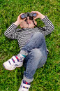Young boy lying on his back with binoculars a green grassy lawn looking at the sky as he views the clouds and watches for birds Stock Images