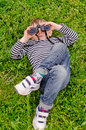 Young boy lying on his back with binoculars a green grassy lawn looking at the sky as he views the clouds and watches for birds Stock Photo