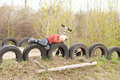 Young boy lying on old tyres playful spread out along the top of which are inserted upright into the ground bordering a rural road Stock Images